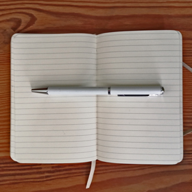 Photograph of an open notebook with a pen lying across empty pages.